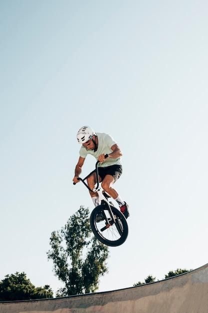 Joven ciclismo en tiro de ángulo bajo skatepark Foto gratis