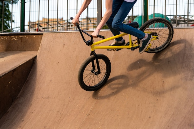 Joven ciclista bajando la rampa. guy está rodando por la bicicleta desde la rampa. Foto Premium