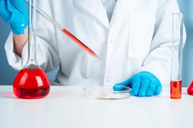 Joven científico con probeta haciendo investigación en laboratorio clínico, especialista profesional en ciencias en el trabajo, Foto Premium