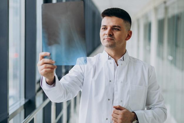 Joven cirujano guapo mirando la radiografía Foto gratis