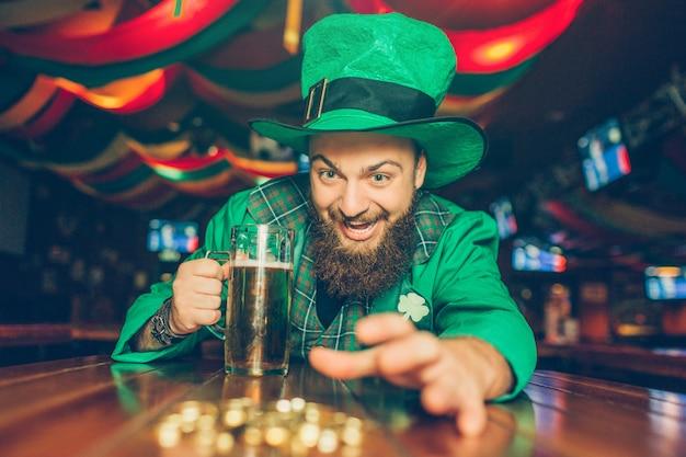 Joven codicioso en traje verde de san patricio alcanzando monedas de oro. lo pone a la mesa en el pub y sostiene una jarra de cerveza. Foto Premium