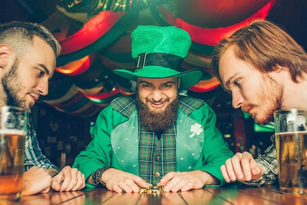 El joven codicioso en traje verde se sienta a la mesa con amigos y mira las monedas de oro que agarró. otros chicos los miran también. tazas de cerveza de pie sobre la mesa. Foto Premium