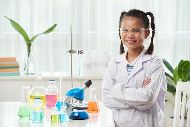 Joven colegiala asiática posando en clase de química con viales de colores Foto gratis