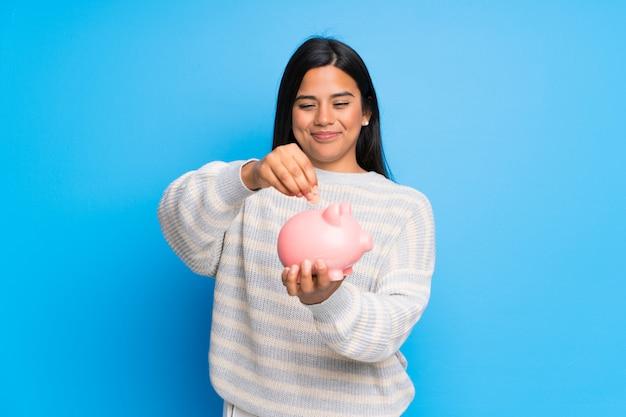 Joven colombiana con suéter tomando una alcancía y feliz porque está llena Foto Premium