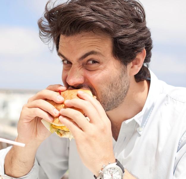 Joven comiendo una hamburguesa Foto Premium
