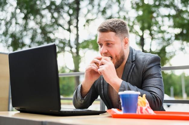 Joven comiendo mientras mira portátil Foto gratis