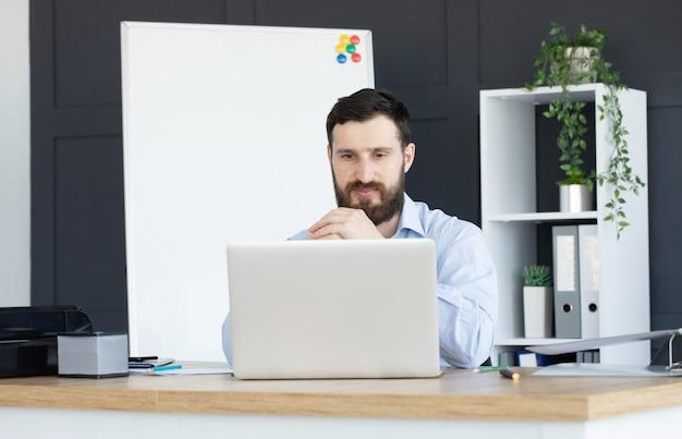 Joven concentrado trabajando en equipo portátil en la oficina en casa Foto Premium