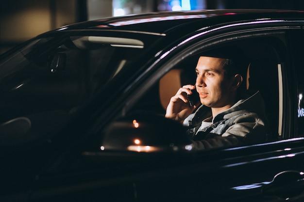 Joven conduciendo su automóvil por la noche y hablando por teléfono Foto gratis