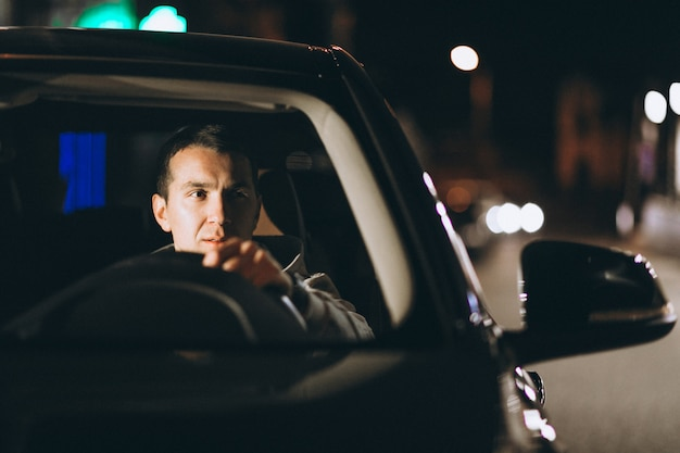 Joven conduciendo su automóvil por la noche Foto gratis