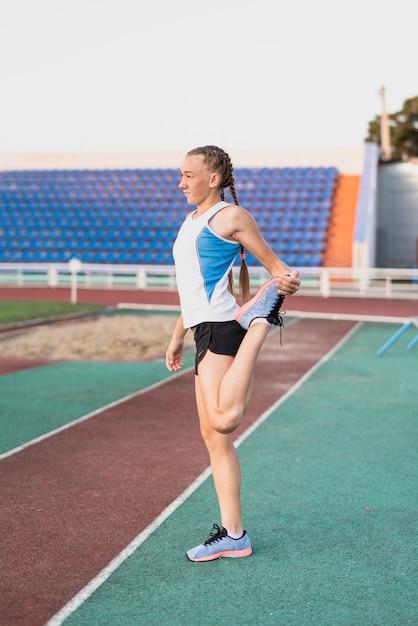 Joven corredor calentando antes del maratón Foto gratis