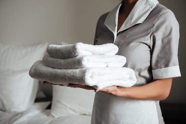 Joven criada del hotel de pie y sosteniendo toallas limpias y frescas Foto gratis