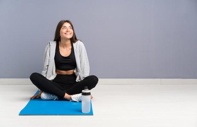 Joven deporte mujer sentada en el suelo con estera riendo y mirando hacia arriba Foto Premium