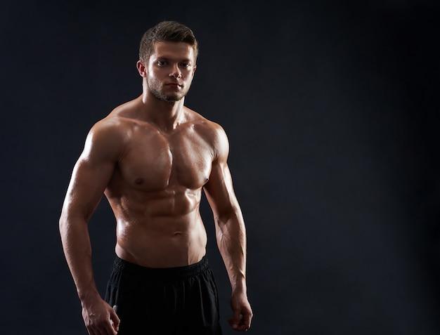 Joven deportista en forma muscular posando sin camisa sobre fondo negro Foto gratis