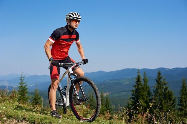 Joven deportista profesional atlético comenzando bicicleta de ciclismo en la cima de la colina Foto Premium