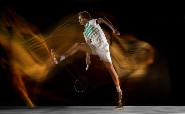 Joven deportista profesional caucásico jugando al tenis en la pared negra en luz mixta Foto gratis