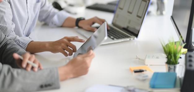 Joven desarrollador web profesional de iu trabajando en su proyecto con computadora portátil y tableta Foto Premium