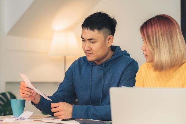 Joven destacó a una pareja asiática administrando las finanzas, revisando sus cuentas bancarias usando una computadora portátil Foto gratis
