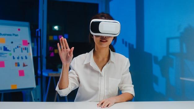 Joven diseñadora asiática usando gafas vr (realidad virtual) probando la aplicación móvil de desarrollar software en la moderna noche creativa de la oficina en casa distanciamiento social, cuarentena para la prevención del coronavirus. Foto gratis