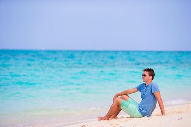 Joven disfrutando de la música en la playa de arena blanca. turista feliz relajante en vacaciones tropicales de verano. Foto Premium