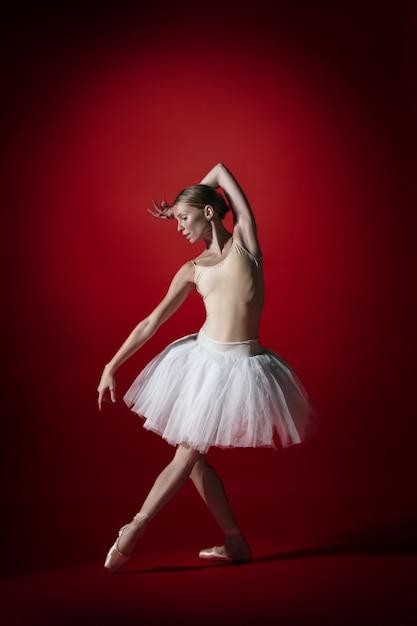 Joven elegante bailarina de ballet clásico o bailarina clásica bailando en el estudio rojo. modelo caucásico en zapatillas de punta Foto gratis