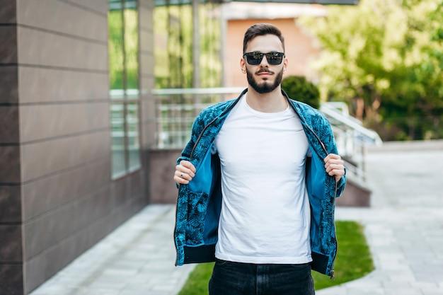 Un joven elegante con barba en una camiseta blanca y gafas de sol Foto Premium