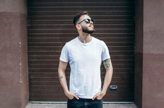 Joven elegante con barba en una camiseta blanca y gafas Foto Premium