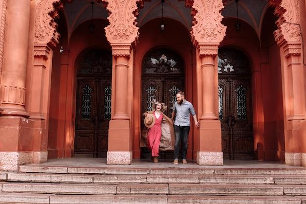 Joven elegante bonita pareja de hipsters enamorados se divierten en la ciudad cerca del castillo en primavera. joven mujer rubia en vestido rojo y hombre con barba están sonriendo en una cita Foto Premium