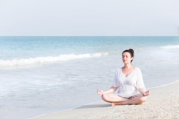 Joven embarazada practicando yoga en el mar Foto Premium