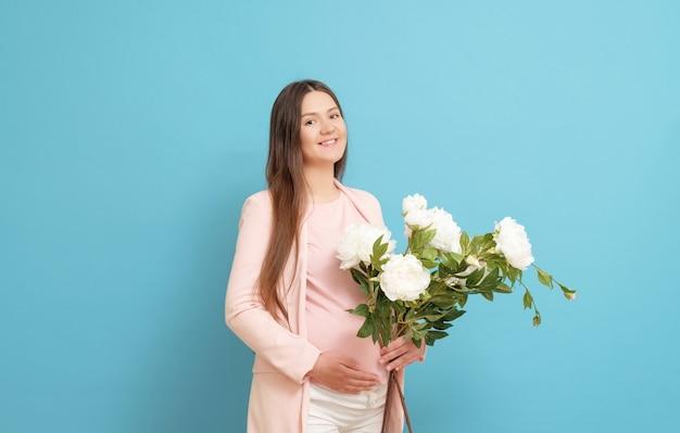 Joven embarazada con un ramo de flores Foto Premium