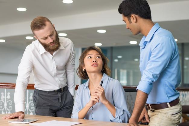 Joven empleado pidiendo ayuda a sus colegas. Foto gratis