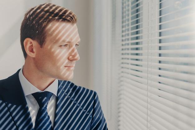 Joven emprendedor en traje rico, piensa en el futuro de su empresa Foto Premium