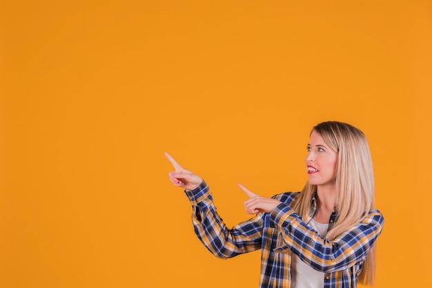 Una joven empresaria apuntando sus dedos contra un fondo naranja Foto gratis