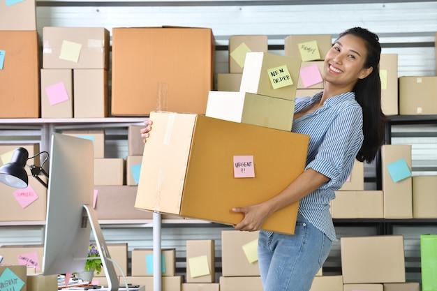 Joven empresaria asiática / dueña de un negocio que trabaja en casa para comprar en línea y preparar un paquete Foto Premium