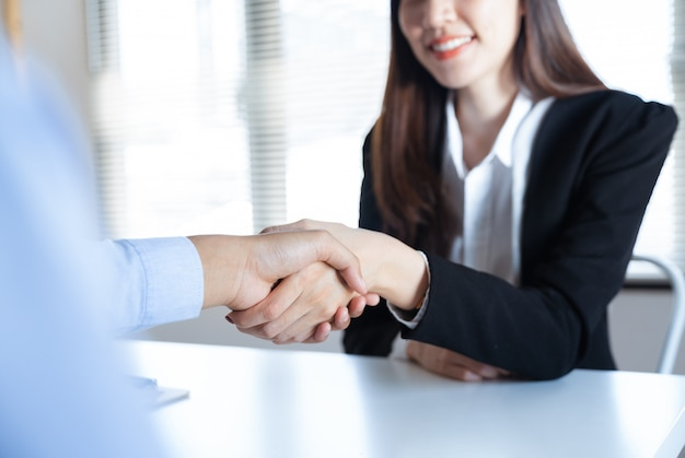Joven empresaria asiática sonriente apretón de manos con el socio empresario haciendo negocios juntos en la oficina de trabajo Foto Premium