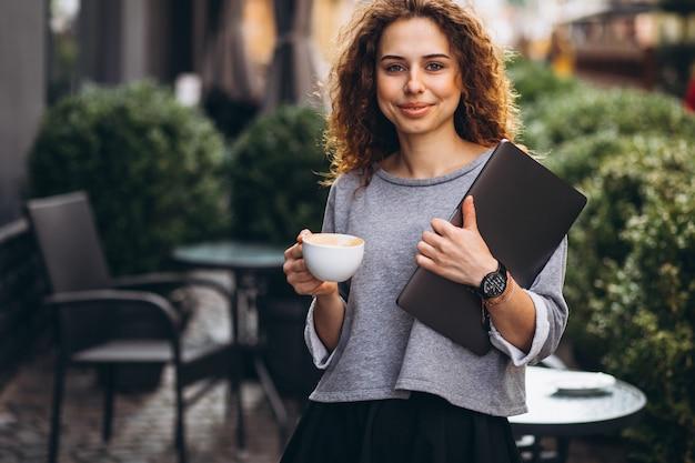 Joven empresaria bebiendo café fuera de café con laptop Foto gratis