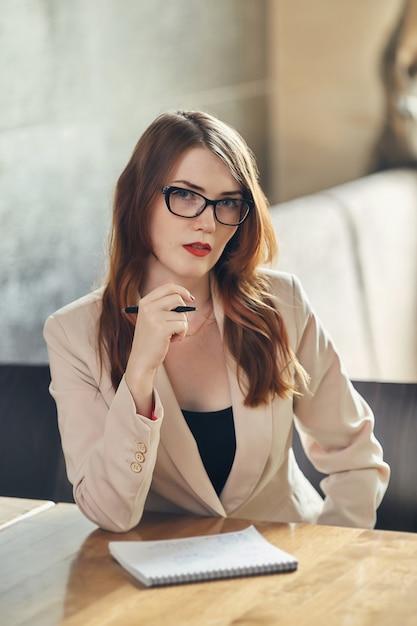 Joven empresaria caucásica con el cuaderno. mujer con gafas en un café Foto Premium