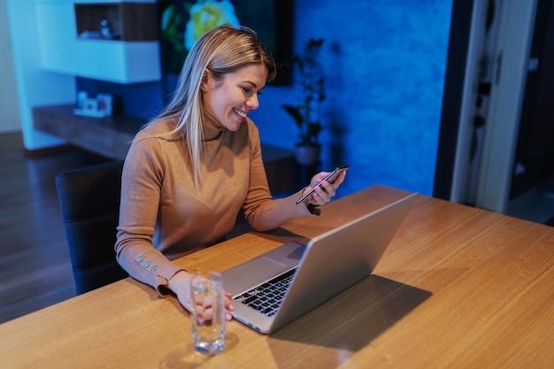 Joven empresaria rubia hermosa sentada en su casa, utilizando teléfonos inteligentes. hay una computadora portátil en la mesa. Foto Premium