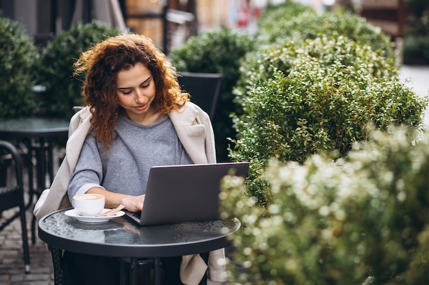 Joven empresaria trabajando en una computadora fuera del café Foto gratis