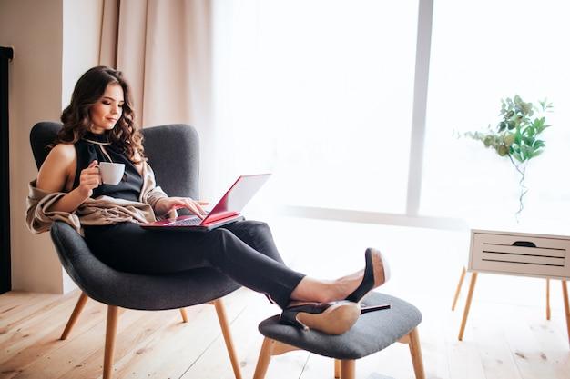 Joven empresaria trabajar en casa. beber café y estudiar. sosteniendo los pies en un taburete pequeño. escribiendo en el teclado del ordenador portátil. modelo ocupado ocupado. solo en la habitación. Foto Premium
