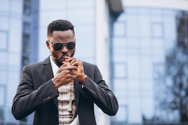 Joven empresario africano en elegante traje fumar cigarrillo Foto gratis