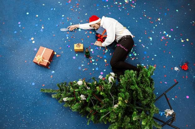Joven empresario celebrando la navidad en la oficina durmiendo en el piso. Foto gratis