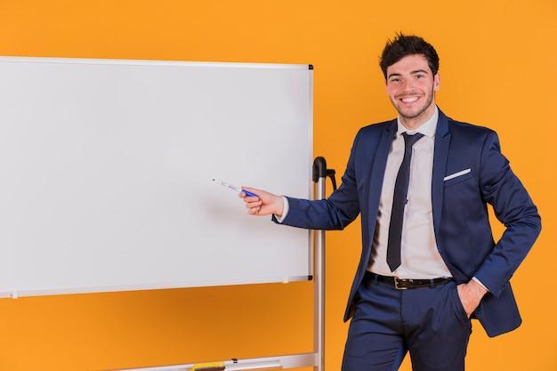 Joven empresario dando presentación contra un telón de fondo naranja Foto gratis
