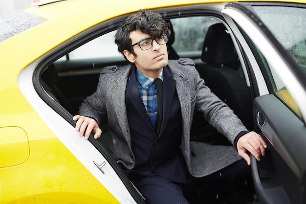 Joven empresario dejando taxi bajo la lluvia Foto gratis