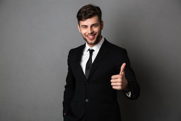 Joven empresario exitoso en ropa formal mostrando el pulgar hacia arriba gesto Foto gratis