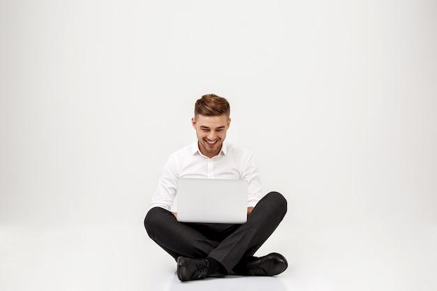 Joven empresario exitoso sonriendo, sentado con el portátil. Foto gratis