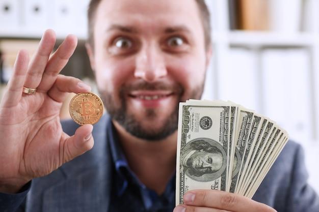 Joven empresario feliz y sonriente que sostiene en la mano dólar y una moneda de bitcoin en lugar de gafas, se alegra de que haya tenido tiempo de comprar para producir el momento antes del aumento de precio y crecimiento. Foto Premium