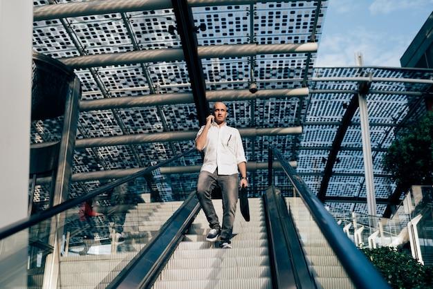 Joven empresario guapo en una escalera mecánica Foto Premium