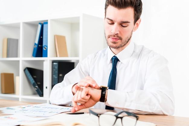 Joven empresario en el lugar de trabajo viendo la hora en el