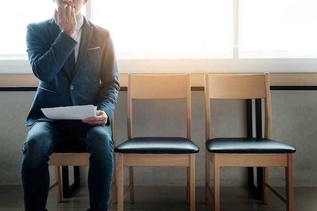 Joven empresario en sala de espera para la entrevista de trabajo ser ansioso, en una fila de sillas. Foto Premium