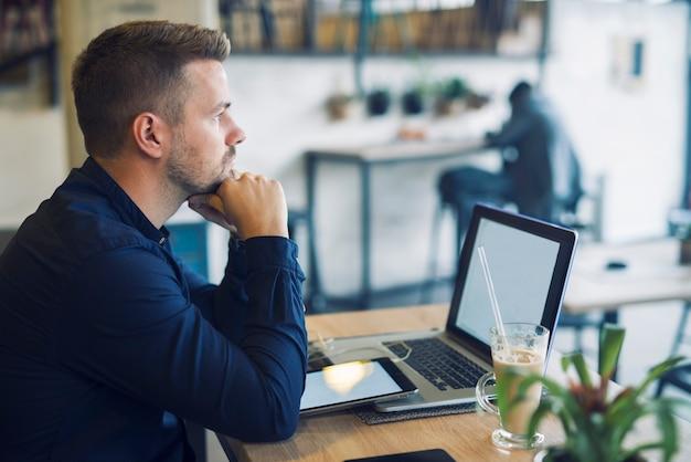 Joven empresario sentado en el café bar con el portátil preocupado y pensando en la solución de su problema Foto gratis